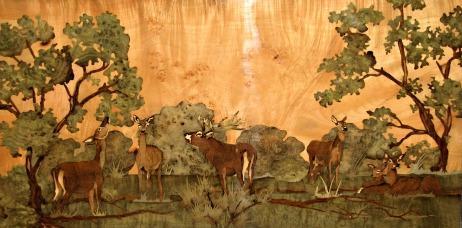 Marqueterie de cerfs et biches dans la forêt.